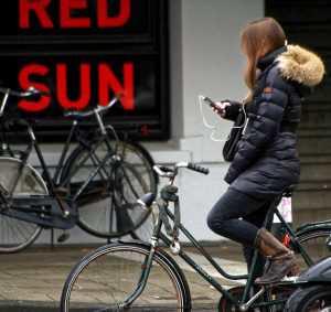 Mädchen mit Handy auf dem Fahrrad